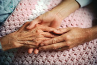 Elderly woman holding hands with loved one